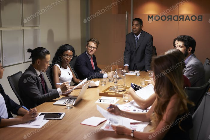 Black businessman standing to address colleagues at meeting