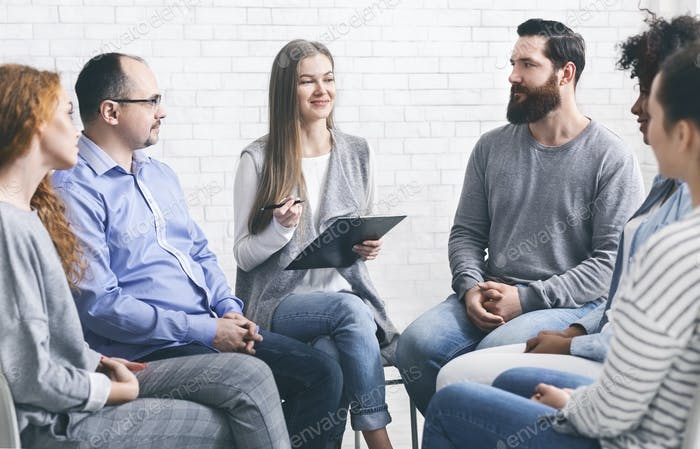 Psychotherapist talking to addicted patients in office