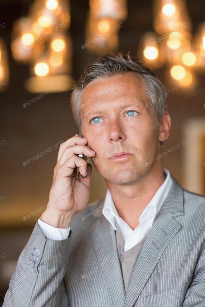 Ernster Geschäftsmann am Telefon im Café