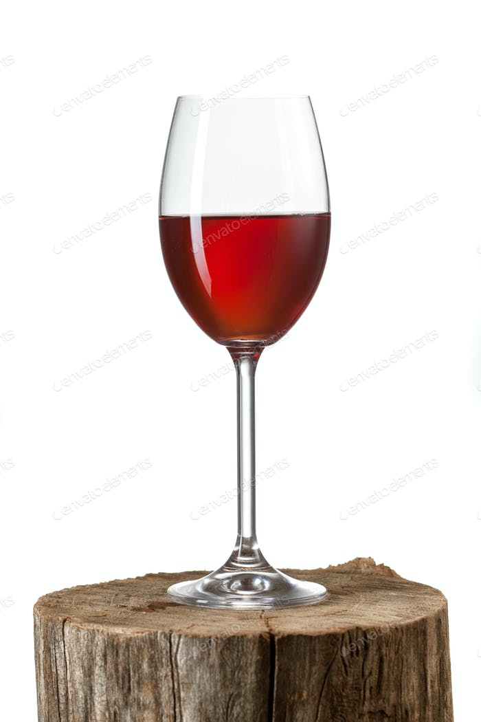 Glass of red wine on stump isolated on white