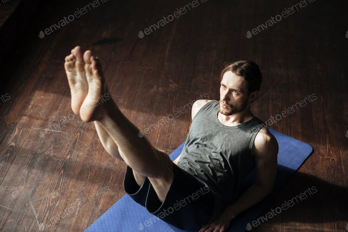 Handsome strong sportsman in gym make yoga sport exercises