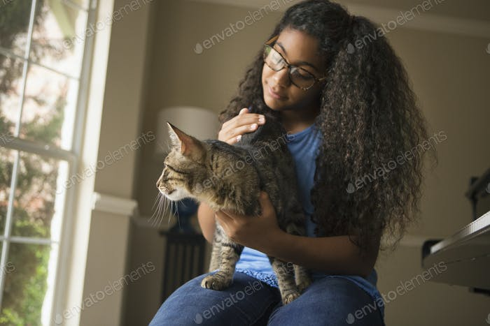 A girl with a cat on her lap.