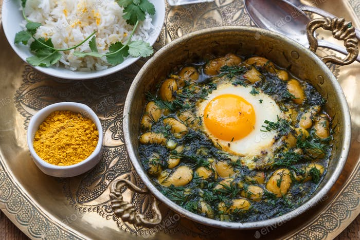Persian breakfast with eggs, bean and dill in copper pan