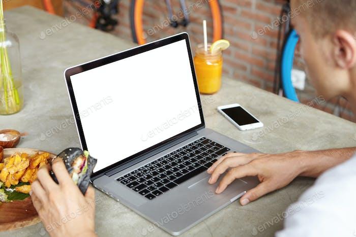 Junger Freiberufler arbeitet remote an seinem modernen Laptop und nutzt kostenloses WLAN, während er Burge isst