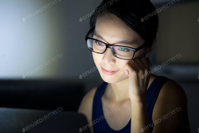 Asian woman look at computer screen at night
