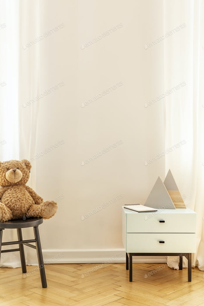 Real photo of an empty wall in a kid room interior with a teddy