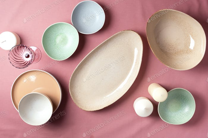 Light pastel colored tableware set: empty serving plates, bowls, candles on pink shabby background