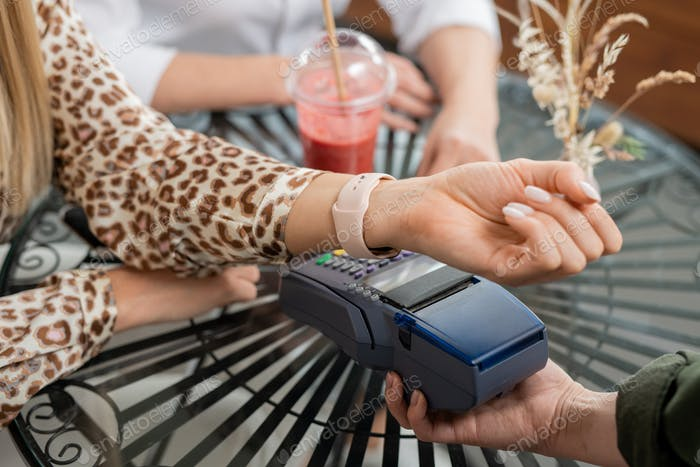 Hand of young woman with smartwatch paying for drinks in cafe