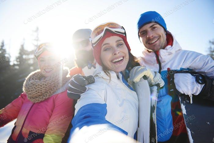 Grupo de cuatro snowboarders felices