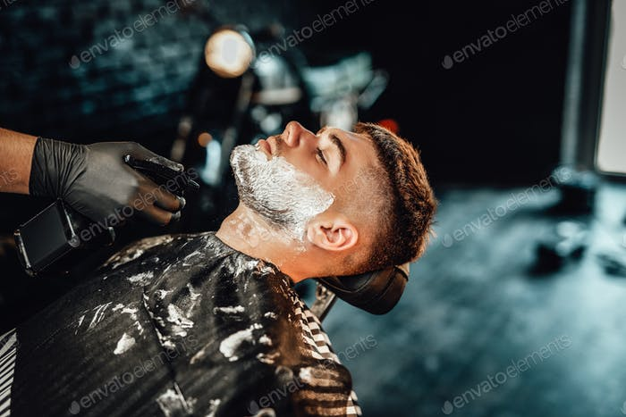 A barber using sprayer to clean his client from soap