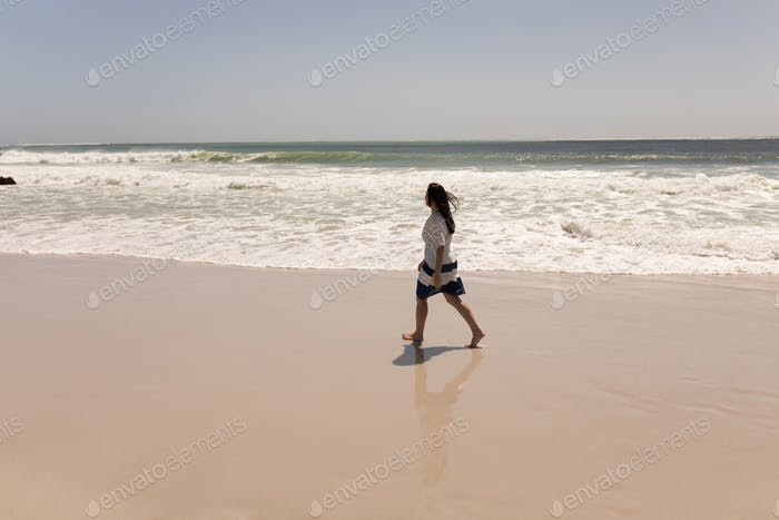 Side view of young woman walking on beach and looking at the horizon in the sunshine