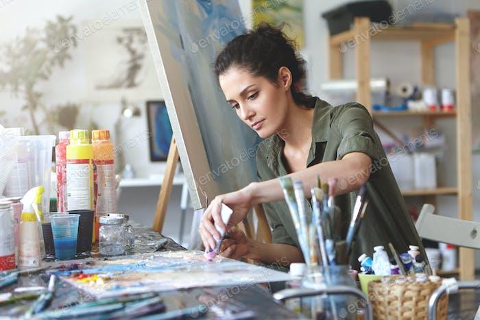 Bild einer ernsthaft konzentrierten jungen kaukasischen Künstlerin, die mit Malaccessiderin am Schreibtisch sitzt