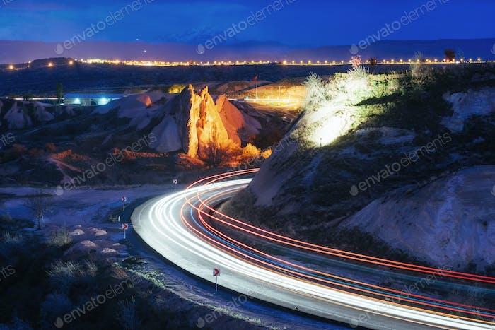 Nachtstraße in den Bergen, die Lichter von den Scheinwerfern