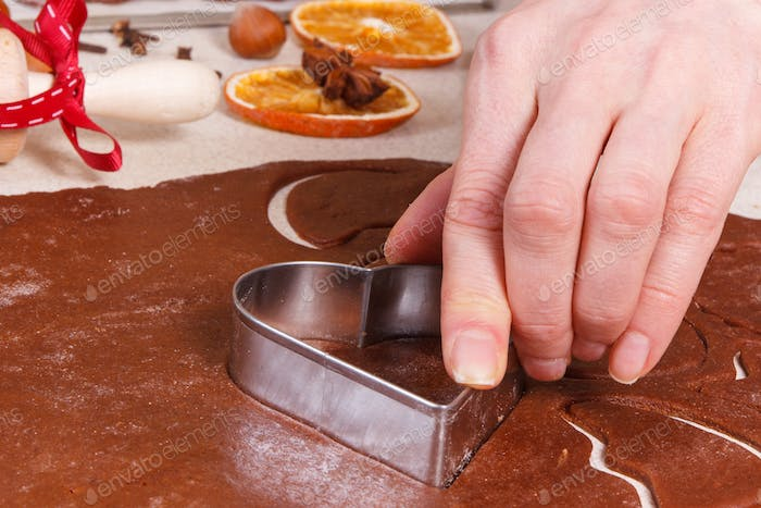 Using cookie cutters and dough for baking festive cookies or gingerbread