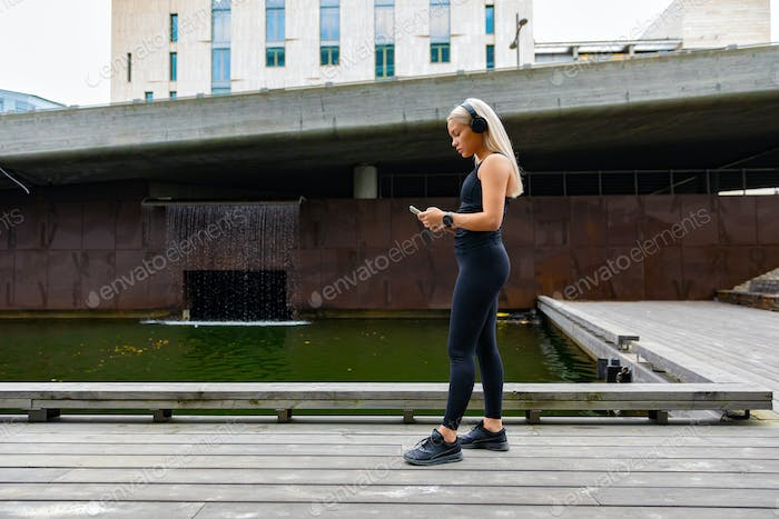 Woman runner start music on smartphone before running