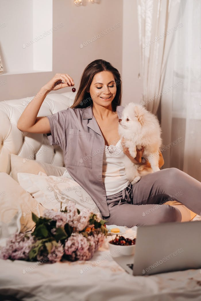 a girl in pajamas sits in bed at night with her white dog watching a laptop and eating sweets.Girl