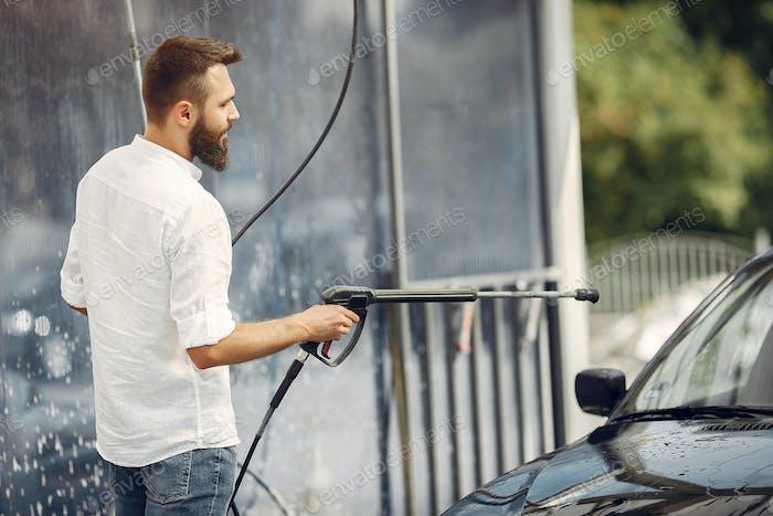 Handsomen man in a white shirt washing his car