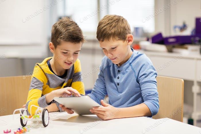 kids with tablet pc programming at robotics school