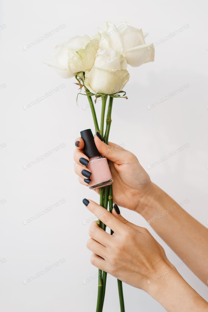 Woman holds nail varnish and flowers, beauty salon