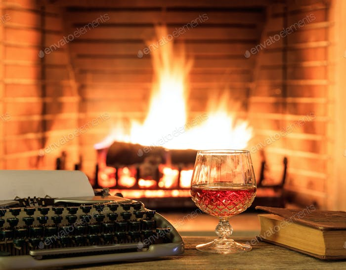 Glass of brandy and a typewriter, logs burning in a fireplace