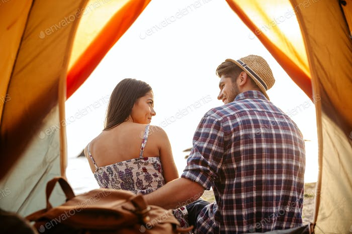 Happy couple sitting at camping tent