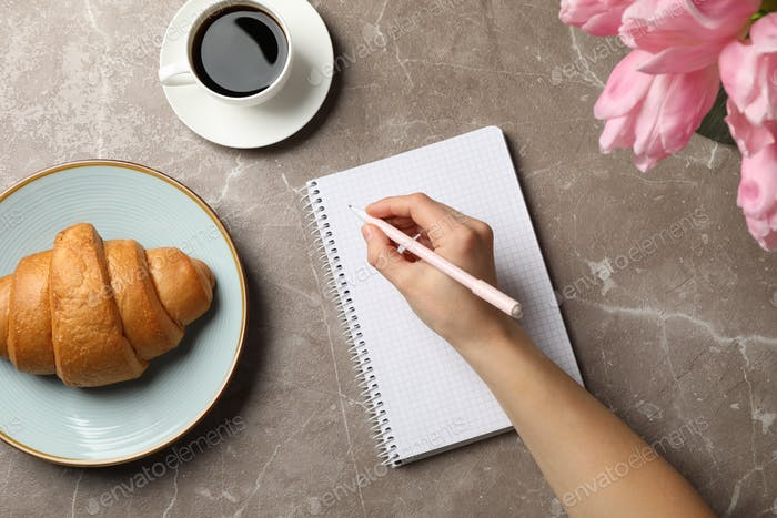 Female hand hold pen on grey background with notebook, coffee, tulips and croissant, top view