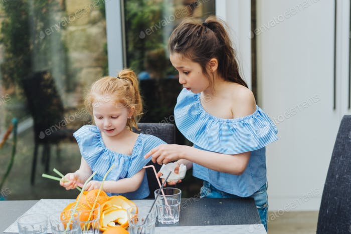 Two sisters drink juice in the kitchen