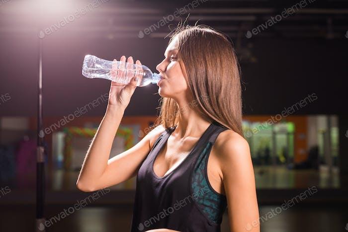 Fitness Frau Trinkwasser aus der Flasche. Muskulöse junge Frau im Fitnessstudio eine Pause vom Training.