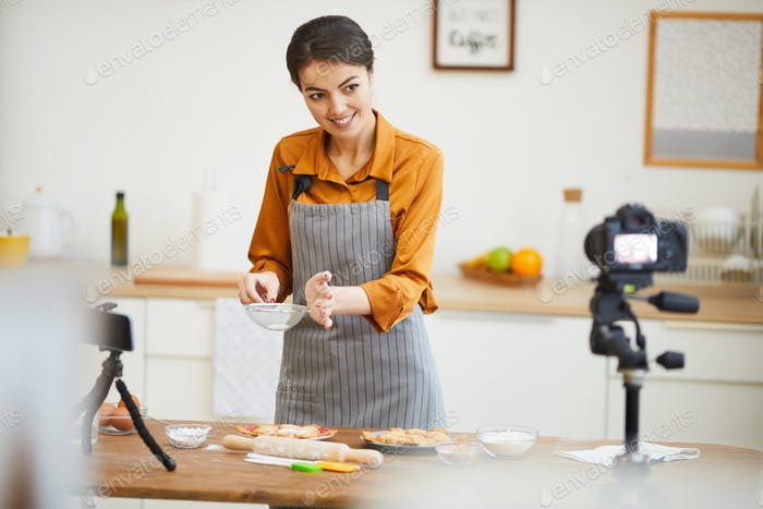 Young Woman Filming Baking Tutorial in Kitchen