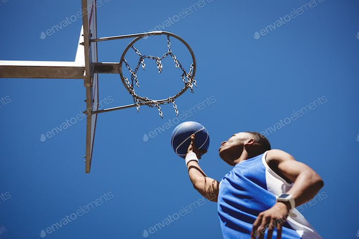 Low angle view of teenage boy playing basketball