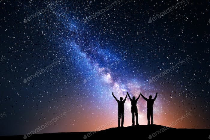 Landscape with Milky Way and silhouette of a happy family
