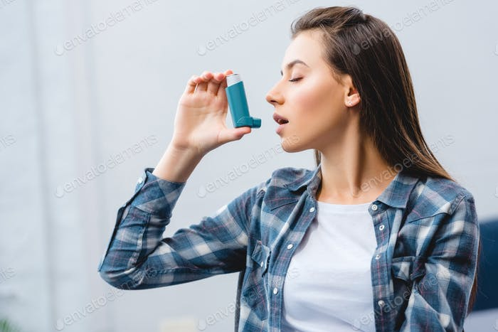 young woman using inhaler while suffering from asthma at home