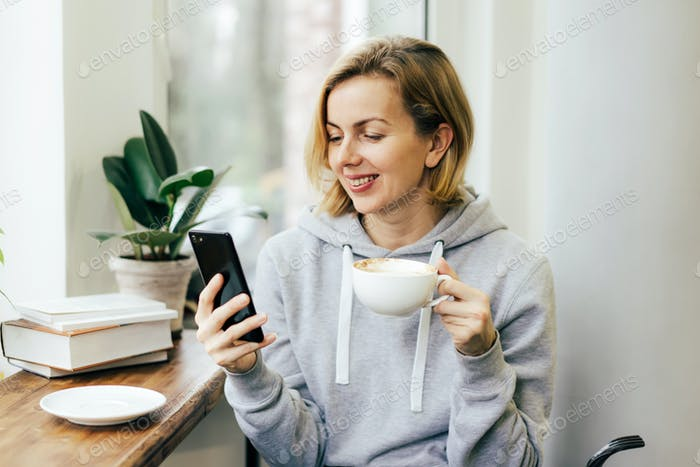 A woman drinks coffee and communicates on a messenger on her phone in a bright cafe by the window.