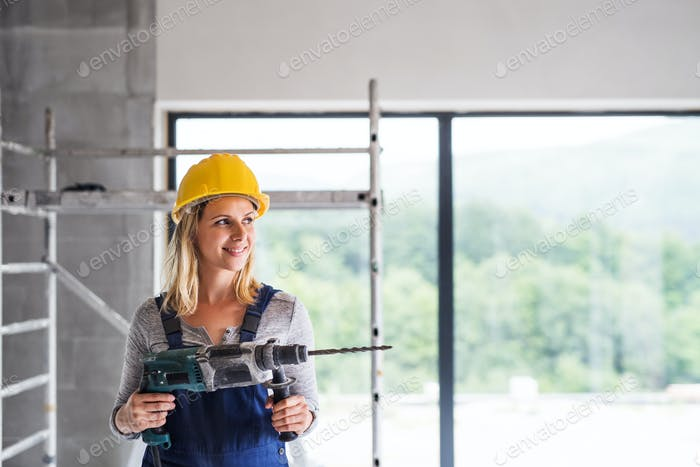 Young woman worker with an electric drill on the construction site.
