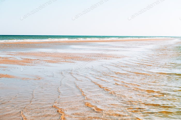 Tide waves on tropical beach sand and blue ocean