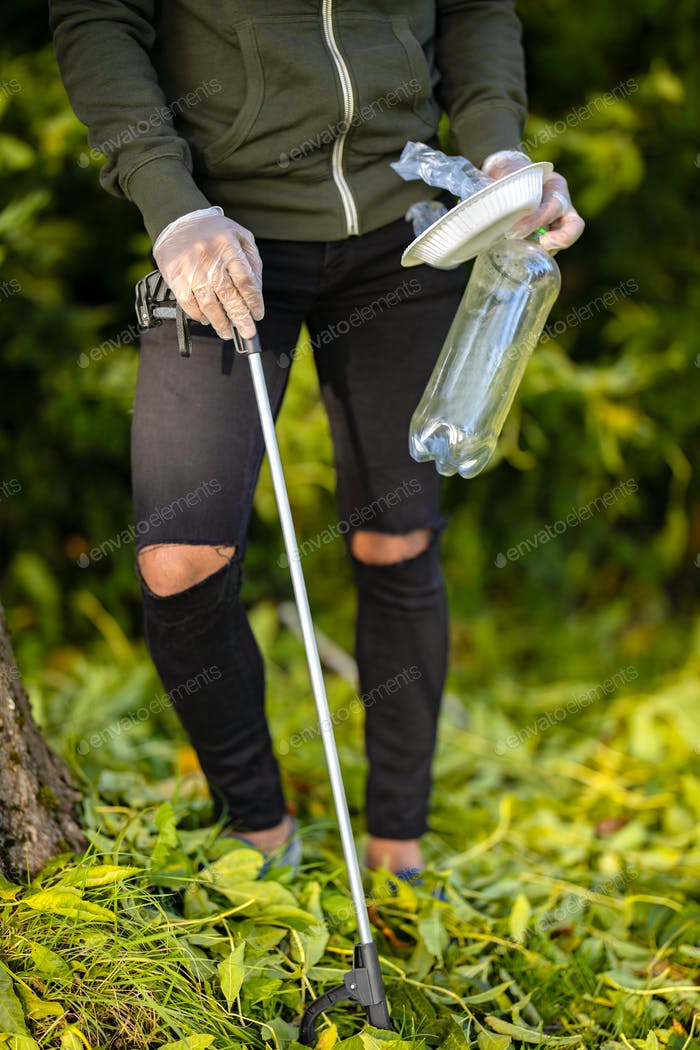 Male volunteer picking up plastic trash from grass