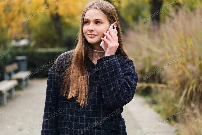 Pretty smiling girl in coat talking on cellphone walking in park