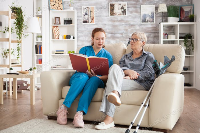 Female care giver reading a story from a book to a senior woman