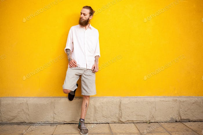 Tattooed bearded man on yellow wall