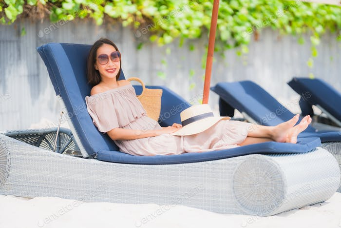 Portrait beautiful young asian woman on the deck chair with umbr