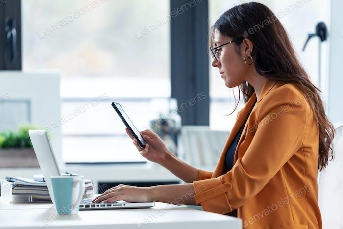 Business junge Frau mit ihrem Handy während der Arbeit mit Laptop im Büro.