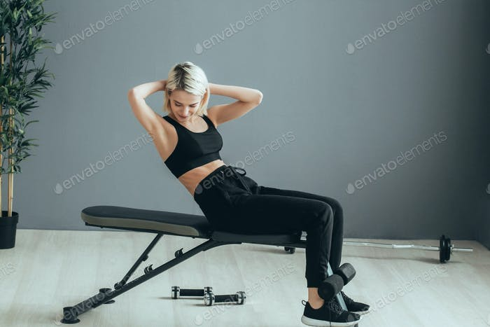 Sport. Woman in sport gym making exercise training. Sporty blonde female with sporty equipment.