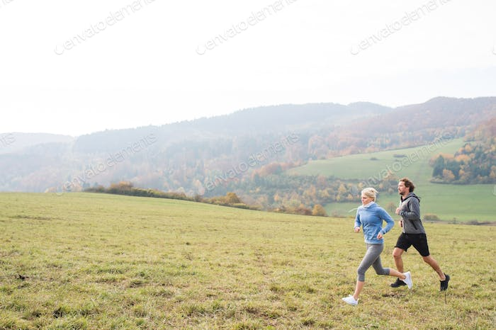 Beautiful young couple running in sunny autumn nature.