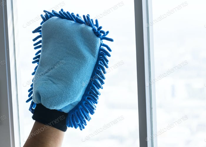 Closeup of hands cleaning window domestic chores concept