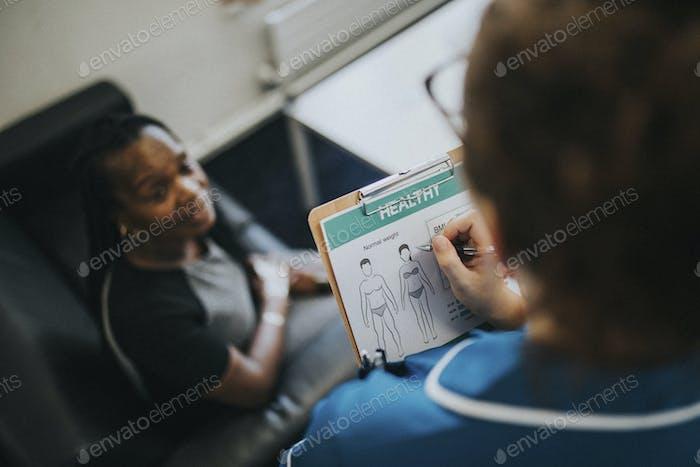 Female nurse jotting down a patients information
