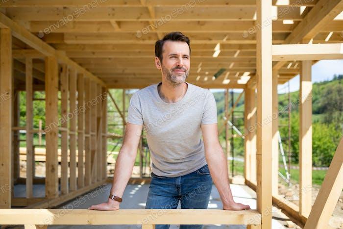 Proud owner of house under construction visit building site, dreams come true