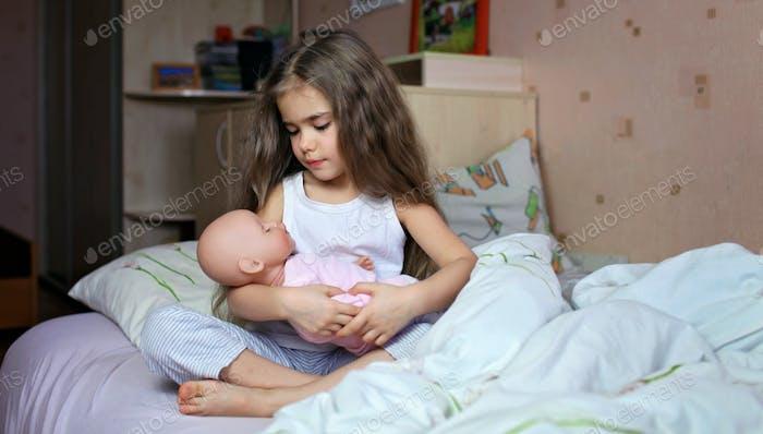 Hübsches Mädchen mit langen Haaren spielt mit Puppe im Bett