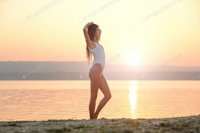Junge Frau in Strings Badeanzug steht am Strand bei Sonnenaufgang
