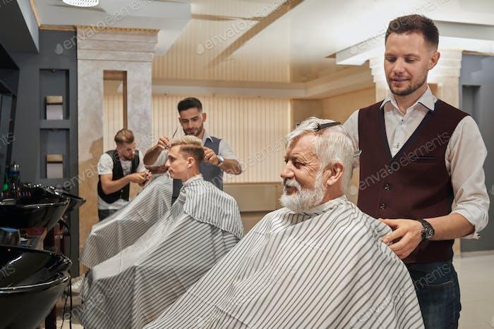 Drei Friseure schneiden und pflegen Haare von Kunden