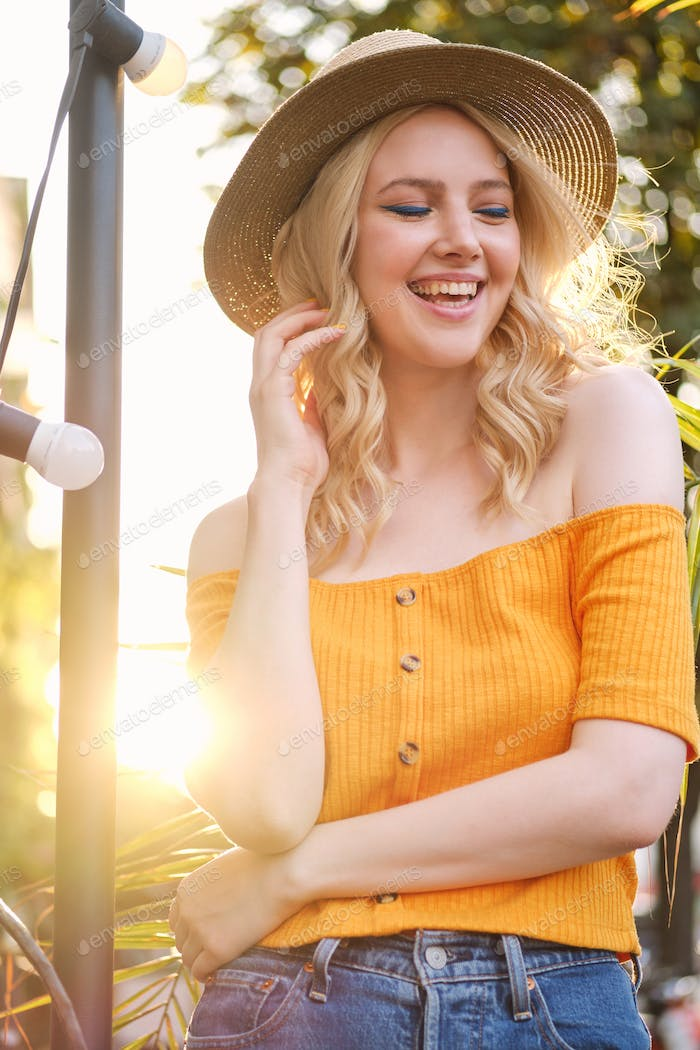 Portrait of cheerful blond girl in hat joyfully laughing standing on city street